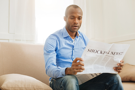 Wow. Concentrated shocked afro-american man holding and reading a newspaper while sitting on the sofa