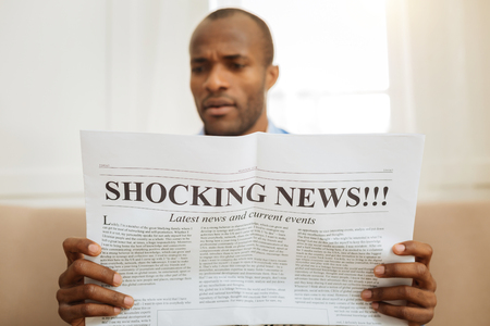 Being astonished. Serious astonished afro-american man holding a newspaper and reading shocking news while sitting on the sofa Stock Photo
