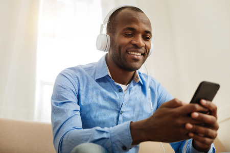 Hobby. Attractive joyful young dark-haired man wearing headphones and holding a phone and listening to music and relaxing