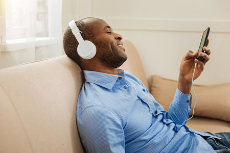 Relaxation. Handsome cheerful young dark-haired man wearing headphones and holding a phone and listening to music while relaxing on the sofa