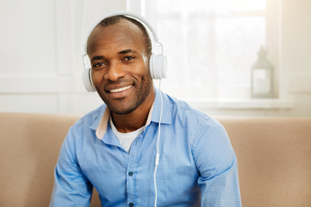 Over the moon. Handsome happy young dark-eyed man smiling and wearing headphones and listening to music while relaxing at home Stock Photo