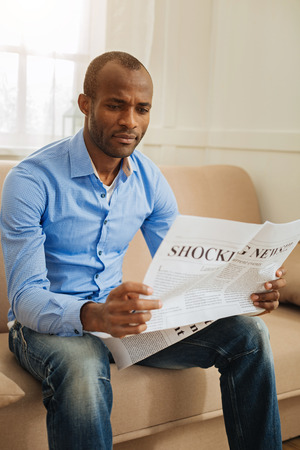 Terrible news. Concentrated bewildered afro-american man holding and reading a newspaper while sitting on the couch
