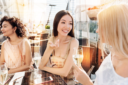 Female talks. Beautiful nice delighted women sitting together and having a conversation while drinking champagne
