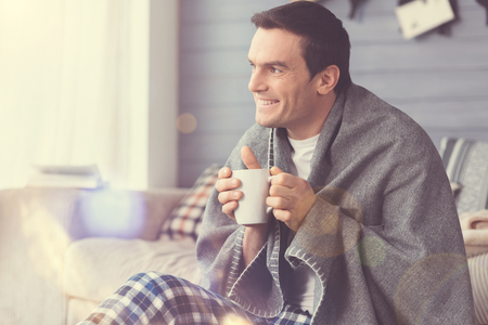 Lovely moment. Nice attractive positive man sitting in the living room wrapped in blanket and drinking coffee Banco de Imagens