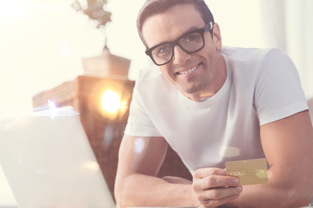 No shops needed. Positive nice smiling man paying for goods he buying in internet using his credit card