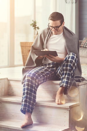 Always online. Active talented committed specialist dedicating his morning to working from home while using his gadget Stock Photo
