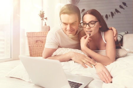 Exciting episode. Charismatic engaging young people using the laptop for enjoying their favorite film while spending morning in bed Stock Photo
