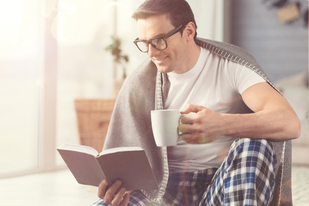 Intelligent hobby. Charismatic charming thoughtful guy spending time at home reading his favorite book and sipping freshly brewed coffee
