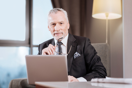Online newspaper. Merry confident senior man has laptop while sitting against blurred background and holding glasses