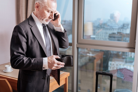 Bill please. Calm pensive senior man holding his wallet while standing and talking on the phone 版權商用圖片 - 92414151