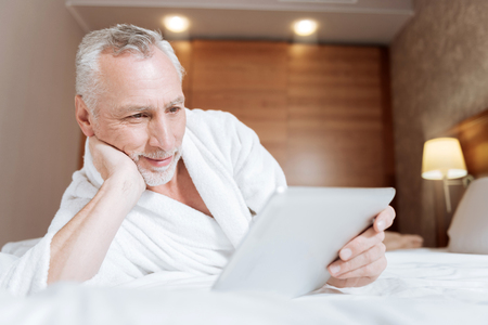 Funny serial. Joyful pretty senior man relaxing on the bed while smiling and posing on the blurred background Stock Photo