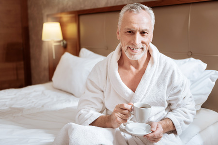 Coffee smell. Senior handsome pleasant man drinking morning coffee while wearing bathrobe and smiling to the camera