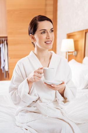 Another day.  Pensive inspired pleasant woman  looking aside while  sitting on the bed and sipping tea Banco de Imagens