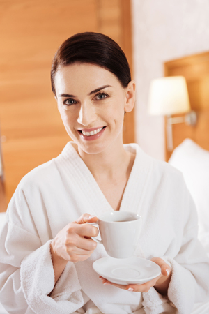 Cup of coffee. Portrait of gorgeous cheerful marry woman drinking coffee  carrying cup while looking straight Banco de Imagens
