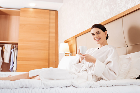 Comfort morning. Low angle of good looking cute emotional woman enjoying tea while smiling and lying at the hotel