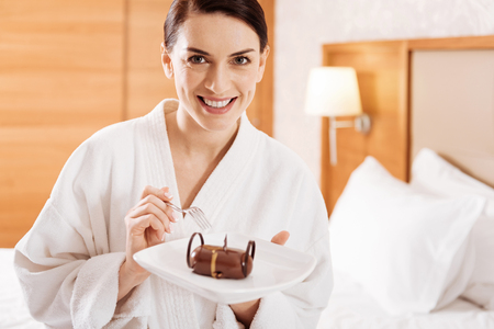 Classic breakfast. Pretty cute sweet woman holding places where lying cake and wants to eat it Stock Photo