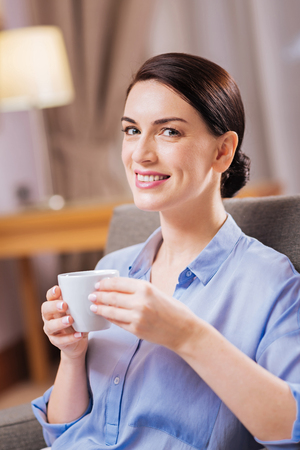 Coffee time. Business professional good looking woman  carrying cup while smiling to the camera and sitting Banco de Imagens