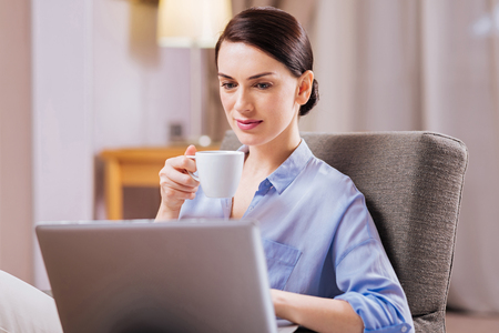 Hard work. Pretty positive young woman sipping tea while sitting and looking at the screen