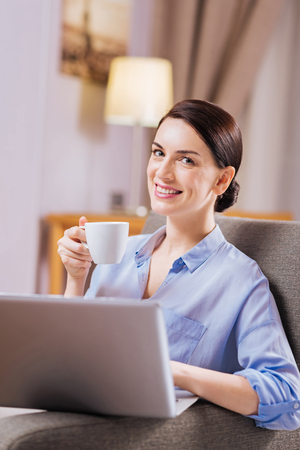 Presentation in process. Joyful merry glad woman typing while smiling and holding cup of coffee Stock Photo