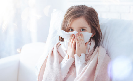 Blow your nose. Pretty child sitting on white furniture and keeping hands near face while looking straight at camera