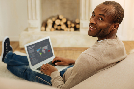 Feeling good. Alert bearded afro-american man smiling and working on the laptop while sitting on the floor and a fireplace in the background Stock Photo