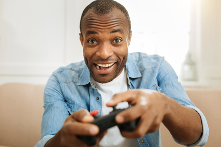 Resting. Good-looking exuberant afro-american man smiling and playing a game with his remote control while sitting on the couch