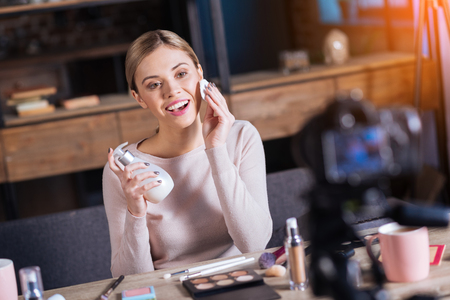 Skin cleansing. Joyful positive nice woman smiling and using a cotton pad while cleansing her skin Stock Photo