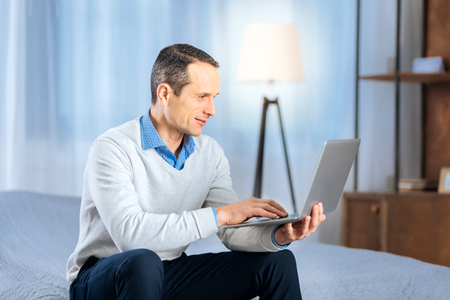 Dedicated worker. Handsome middle-aged man sitting on the bed and working on his laptop while smiling