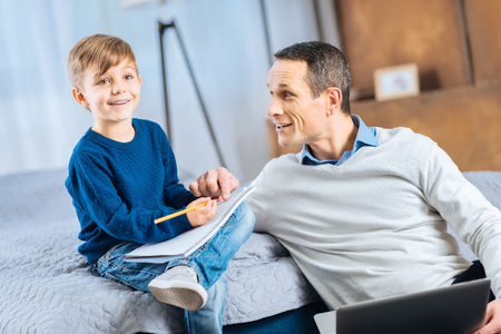 Fresh ideas. Handsome young man sitting on the bedroom floor next to his little son sitting on the bed and discussing the ideas about the future picture