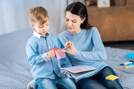Organizing study process. Beautiful young woman sitting on the bed next to her little son and helping him stick memos to the notebook Stock Photo