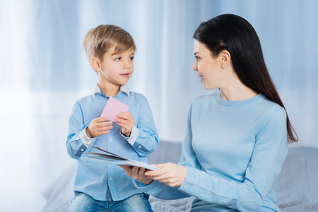 Nice interaction. Charming young woman sitting and her pleasant little son sitting on the bed together and talking while sticking memos to notebook
