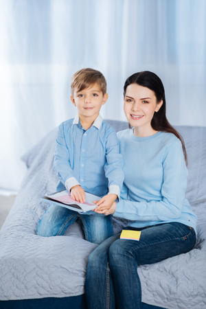 Mother-son bond. Pleasant young woman and her little son sitting on the bed together and posing for the camera while sticking memos to the notebook Stock fotó