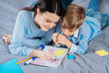 Creative ideas. The top view of a nice little boy lying on the bed next to his mother and watching her draw in a notebook