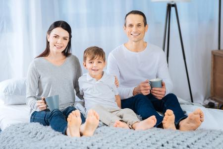 Momenti felici. Bella giovane famiglia seduta sul letto, tenendo tazze da tè e in posa per la fotocamera, sorridendo brillantemente