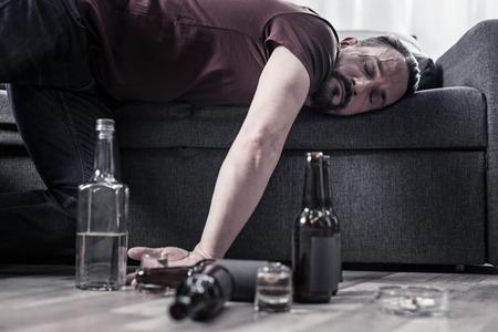 After drinking. Drunk bearded adult man lying on the sofa and sleeping after drinking lots of alcohol