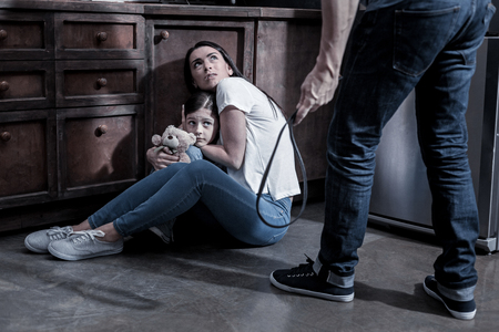 Do not hurt us. Scared unhappy young woman sitting on the floor and hugging her daughter while looking at her husband Foto de archivo