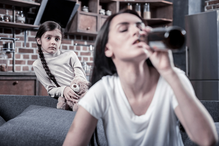 Unhappy childhood. Sad nice cute girl holding her toy and looking at her mother while feeling upset Stock Photo