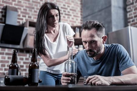 Alcohólico en una familia Brutal barbudo hombre triste sentado frente a la botella de vodka y pensando en sus problemas mientras bebe en casa Foto de archivo