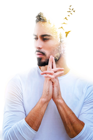 Absolutely free. Handsome pleasant beaded man standing and holding his hands together while imagining birds Stock Photo
