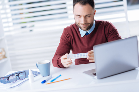 Convenient pillbox. Young calm handsome man sitting in front of a laptop and smiling while looking at the little convenient pillbox in his hands Stock Photo
