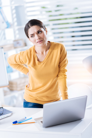 Feeling backache. Young unhappy woman standing near the table at her working place and frowning while touching her back and having a sudden pain in it Stock Photo