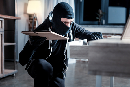 Theft. Dark-eyed serious masked burglar wearing a uniform and holding a folder while looking for something in the table