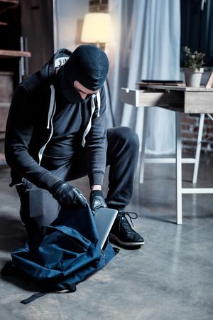 Raub. Schlauer professioneller maskierter Räuber, der eine schwarze Uniform und Handschuhe trägt, einen Laptop stiehlt und ihn in die Tasche steckt Standard-Bild - 93275519
