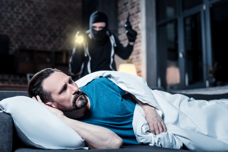 Who is here. Alarmed disturbed bearded man waking up and hearing someone being in his house and a masked criminal with a torch and gun standing behind him Stock Photo