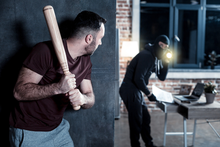 Burglary. Terrified young bearded man hiding and holding a stick while a masked burglar holding a torch and standing at the table and looking for something there Stock Photo