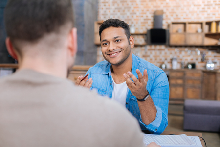 Pleasant smile. Positive happy emotional man sitting at the table and smiling cheerfully while looking at his smart pleasant colleagues