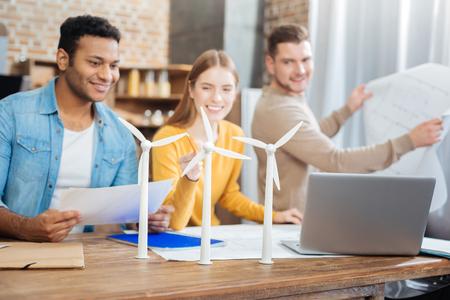 Piccoli mulini a vento. Allegri giovani ingegneri qualificati seduti al tavolo e guardando i minuscoli modelli di turbine eoliche