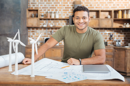 Feeling ready. Clever qualified engineer sitting at the table covered with schemes and drawings and smiling cheerfully while miniature windmill turbines standing by his side