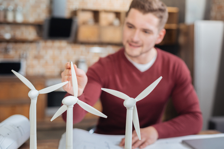 Checking details. Smart professional engineer looking concentrated while sitting in front of tiny windmill turbines and checking their size