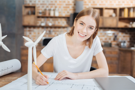 Cute engineer. Lovely positive professional engineer looking happy while sitting at the table with a pencil in her hand and working at the problem of alternative energy